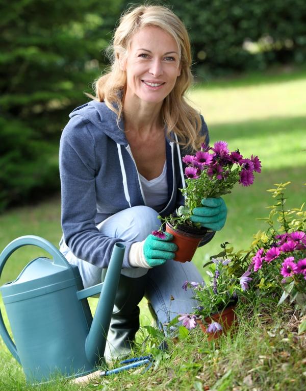 Frau gießt Blumen für Blog